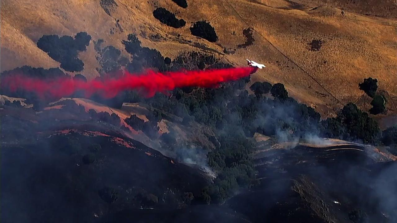 An air tanker is seen dropping retardant on a fire burning in Milpitas, Calif. on Sunday, July 22, 2018.