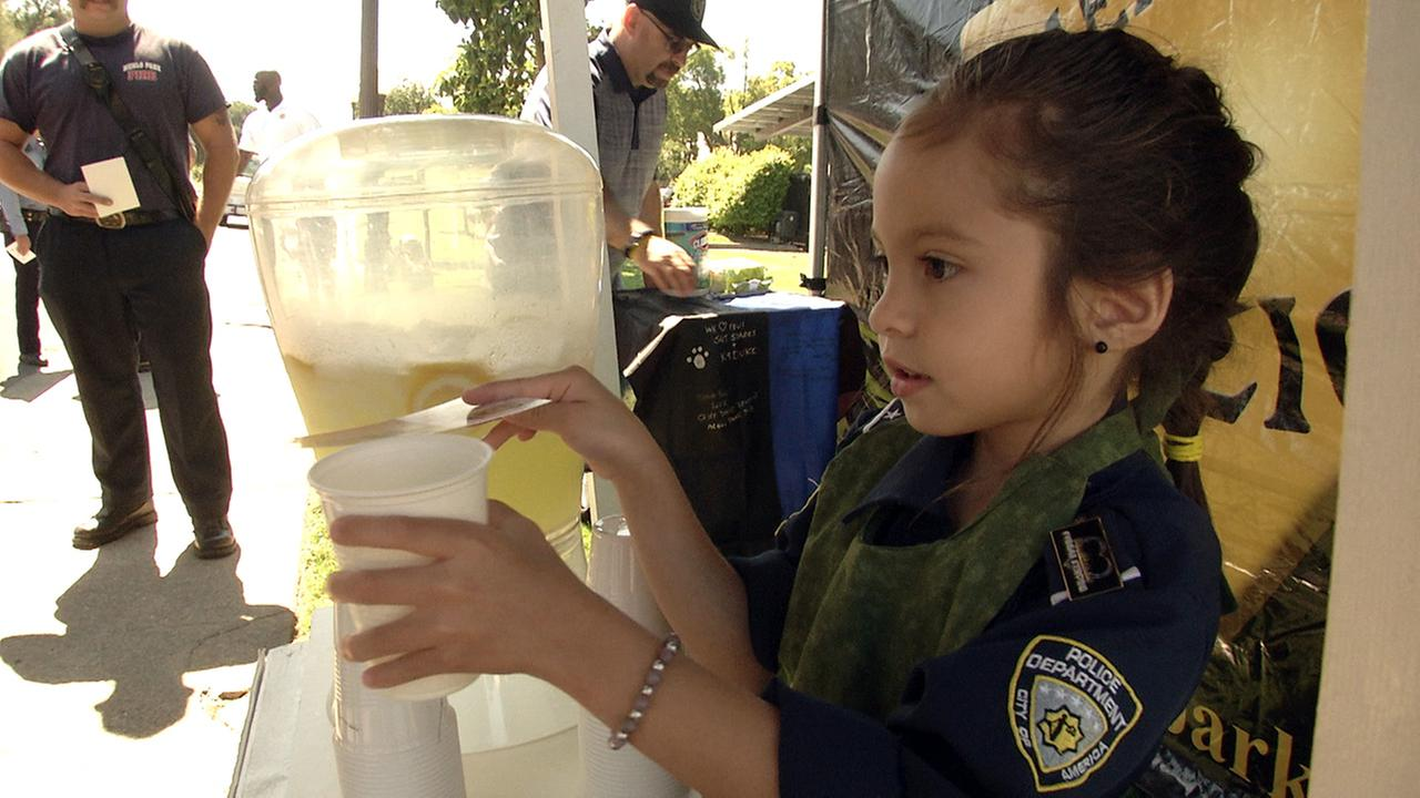 Five-year-old Theresa Ann Babcock serves up some lemonade as part of a fundraiser outside the Menlo Park Police Department.