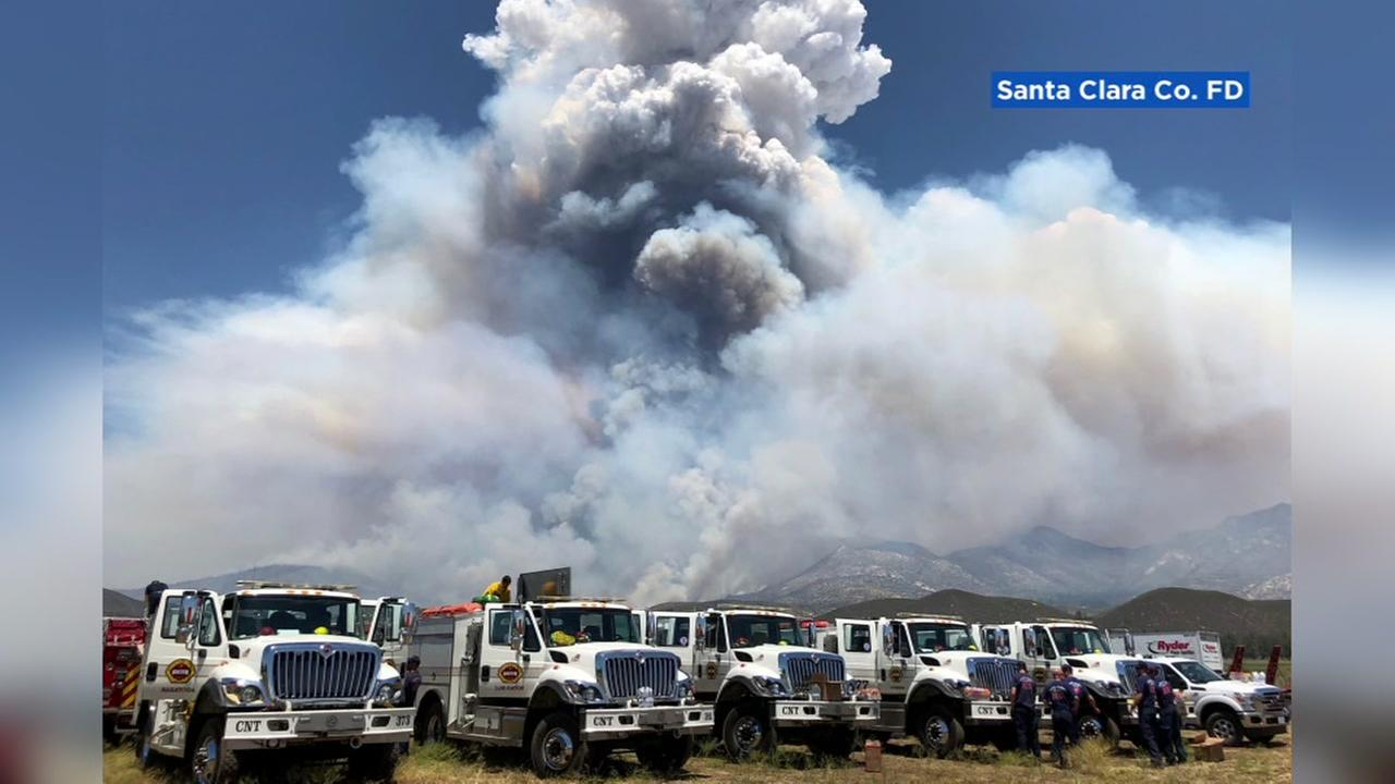 The Santa Clara County firefighters fleet appears in front of a giant plume of smoke.