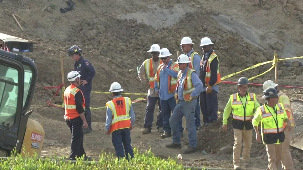 Construction workers stand near a trench that killed one of their fellow workers on Friday, July 27, 2018.