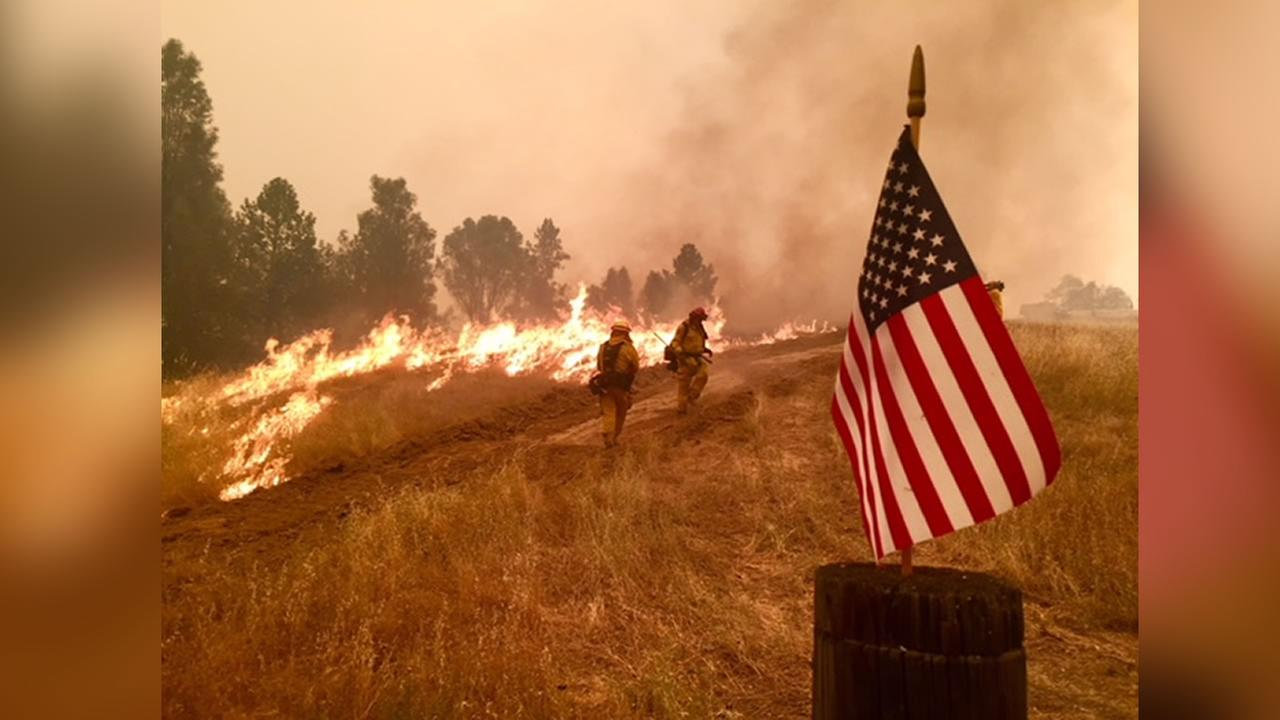An American flag is visible as the Carr Fire burns in Northern California on July 28, 2018.
