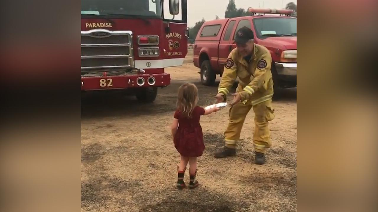 Two-year-old Gracie Lutz hands a burrito to a Cal Fire firefighter battling the Carr Fire.
