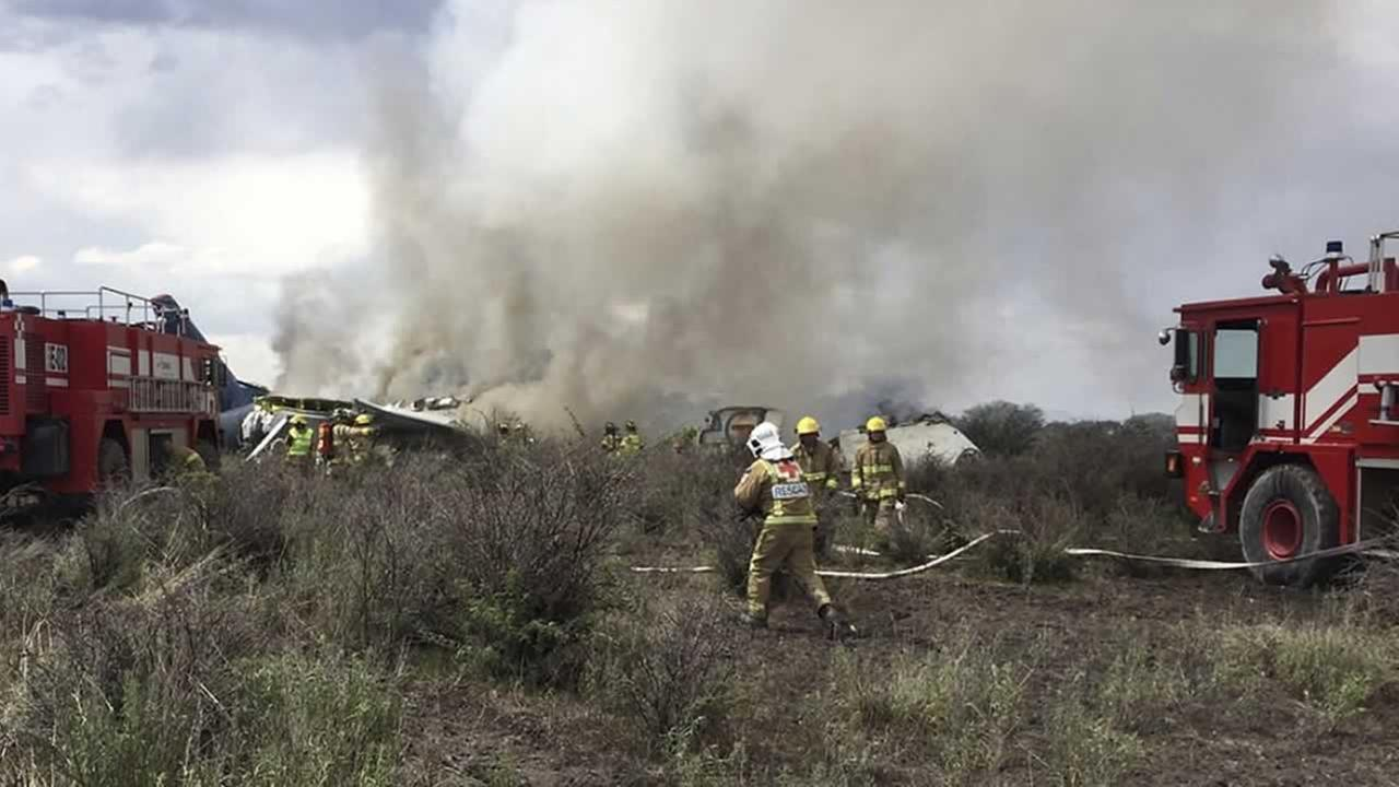 Rescue workers and firefighters are seen at the site where an Aeromexico airliner has suffered an accident in a field near the airport of Durango, Mexico, Tuesday, July 31, 2018.