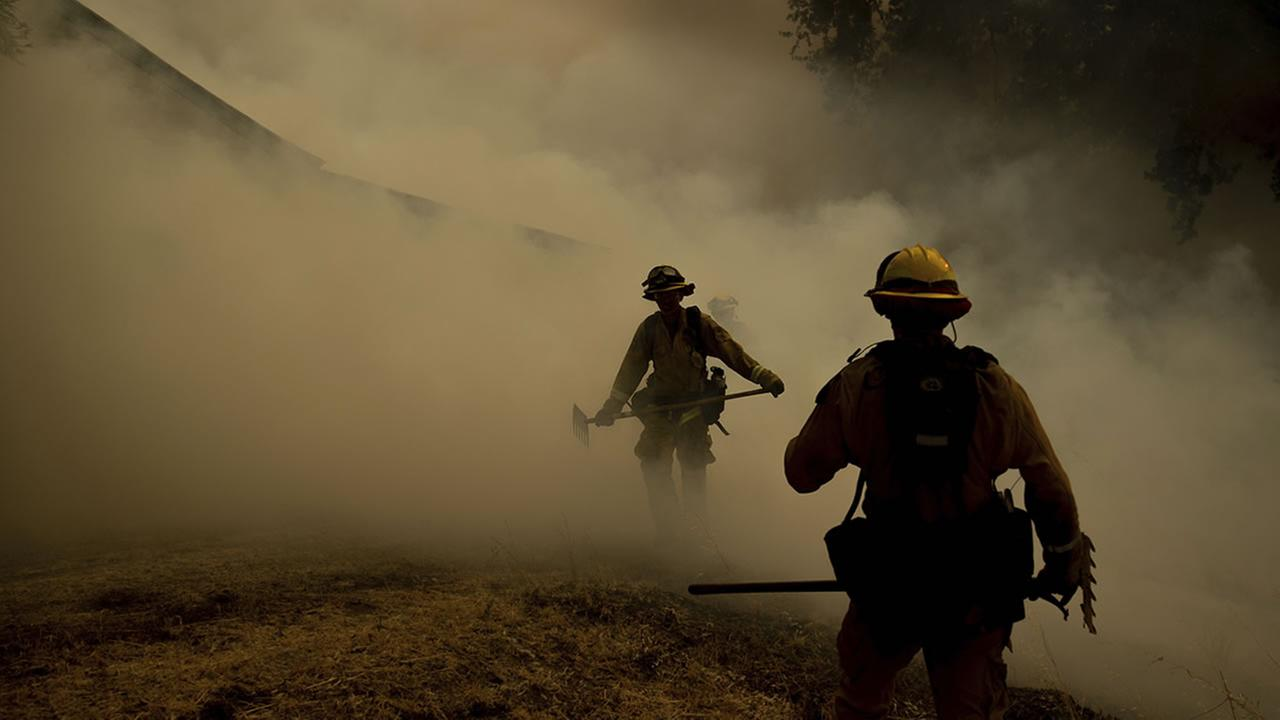 A firefighter walks through smoke while fighting to save Olof Cellars winery in Lakeport, Calif., Monday, July 30, 2018.
