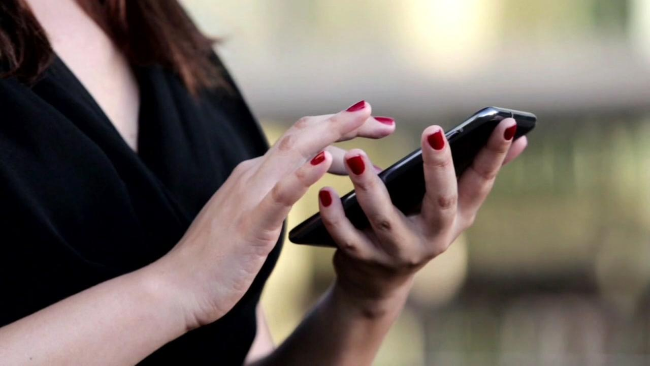 A woman scrolls through her smartphone in this undated file photo.
