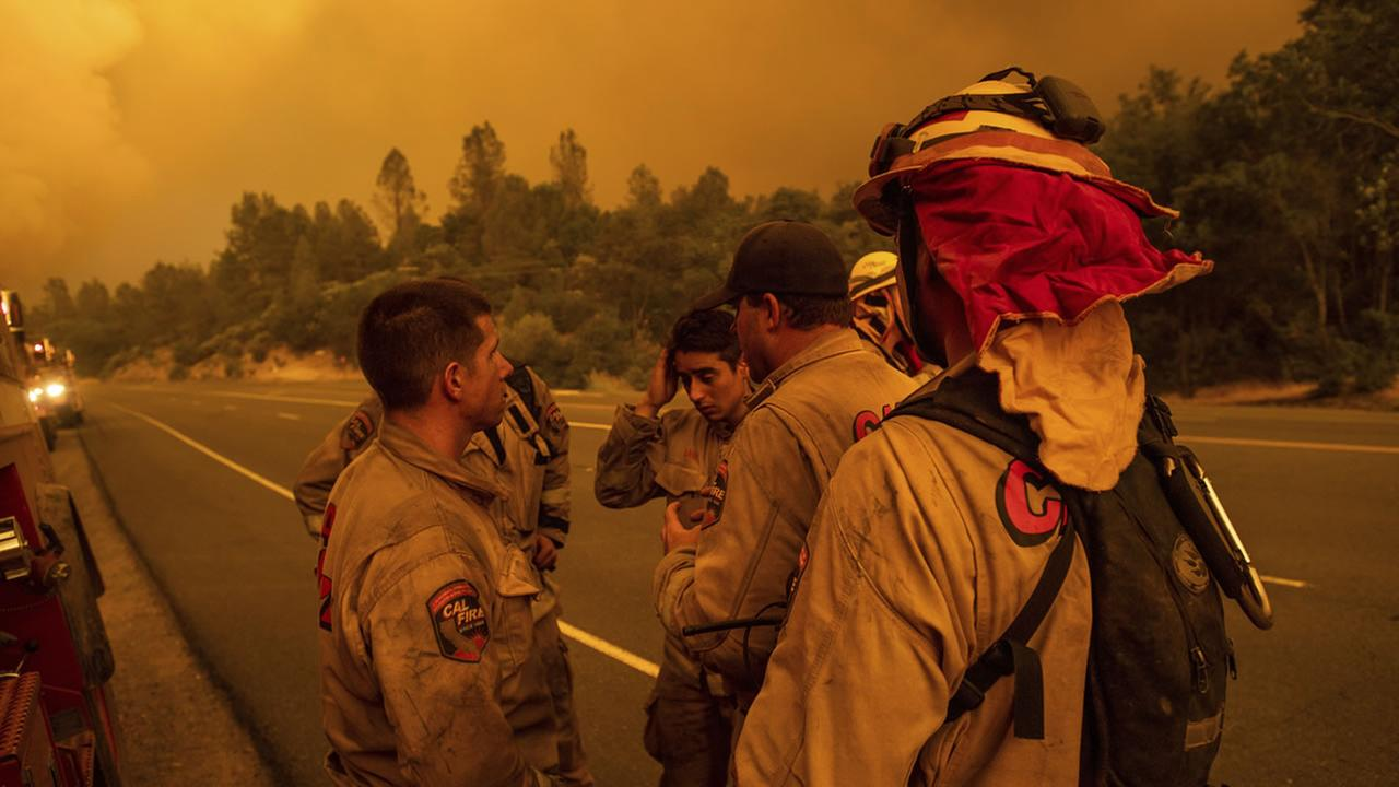 Firefighters discuss plans while battling the Carr Fire in Shasta, Calif., on Thursday, July 26, 2018.