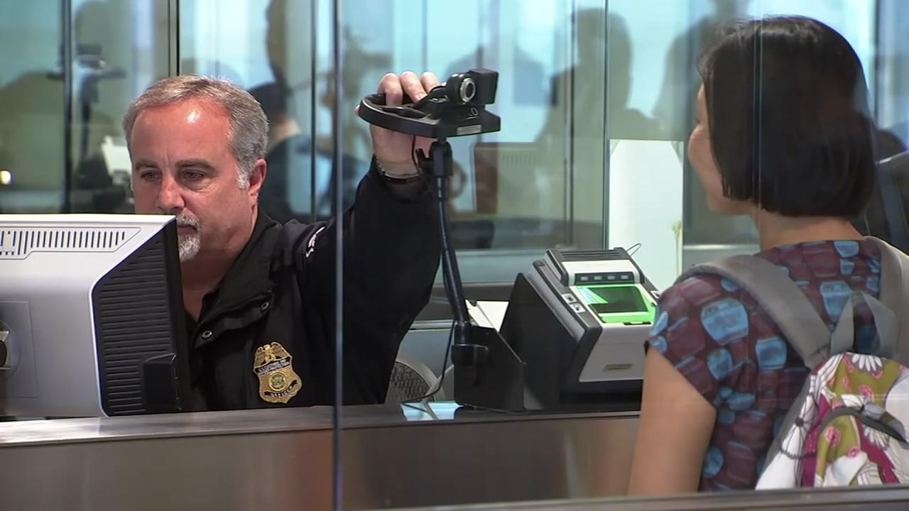 A customs agent is seen taking a picture of a traveler for facial recognition in this undated image.