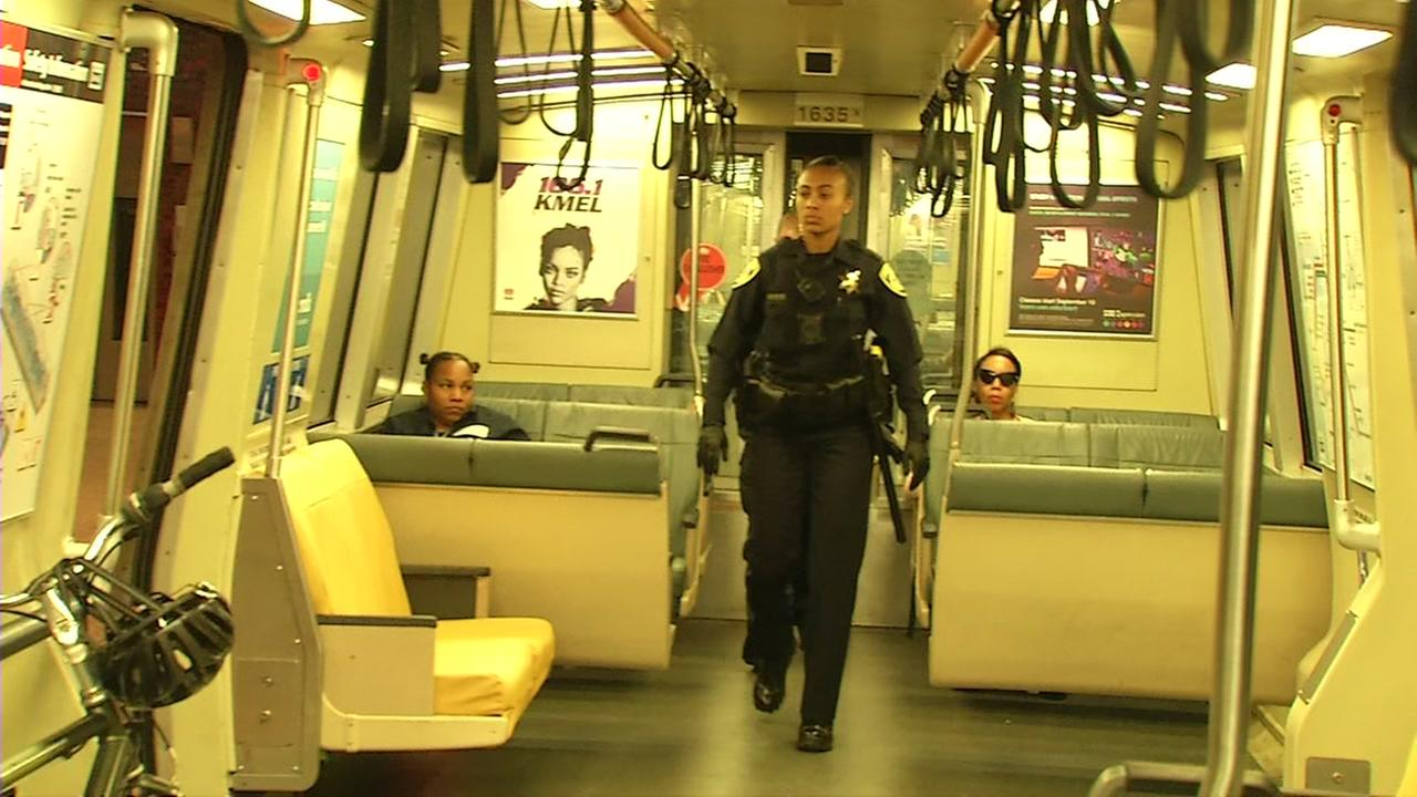 A BART police officer walks through a train car on Monday, August 6, 2018.