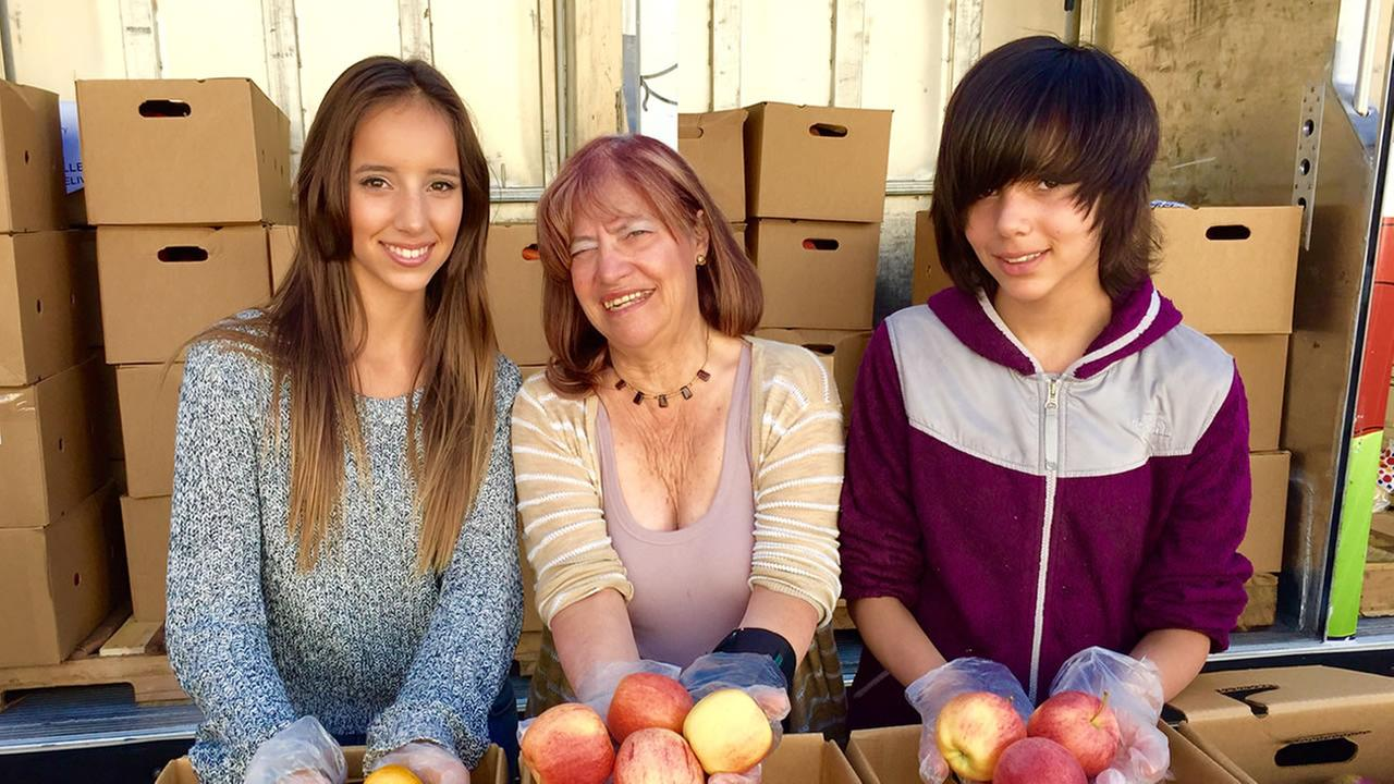 Irene Bender and her daughters hand out food to the needy people in San Carlos.