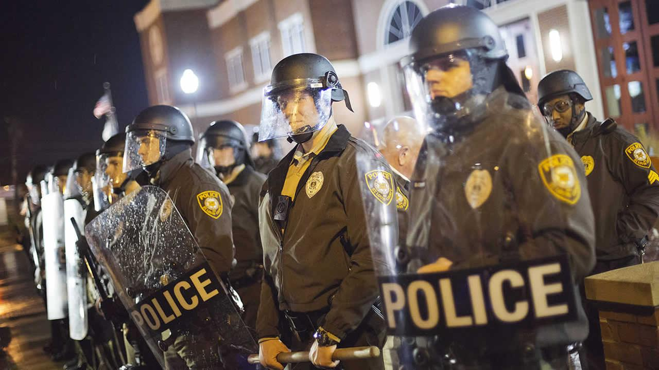 Police stand guard during a demonstration outside the Ferguson Police Department, Sunday, Nov. 23, 2014, in Ferguson, Mo. (AP Photo/David Goldman)