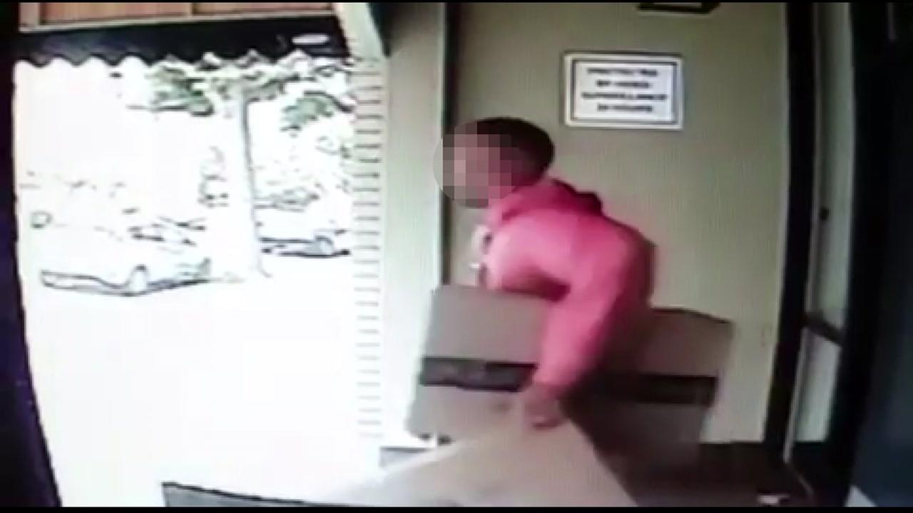 Surveillance footage shows a man carrying packages out of a building in San Francisco.