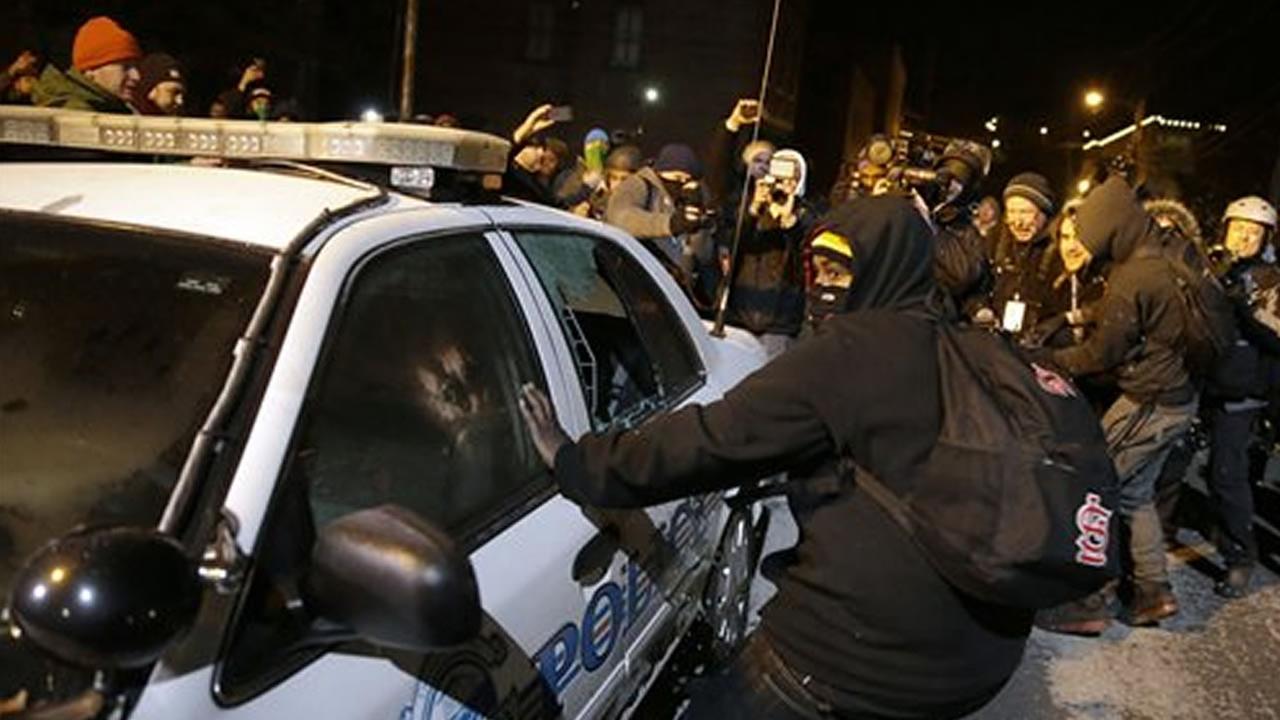 Protesters vandalize a police vehicle near Ferguson City Hall