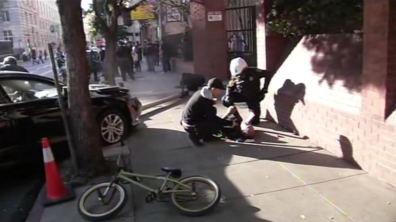 Man laying on ground, car up on curb