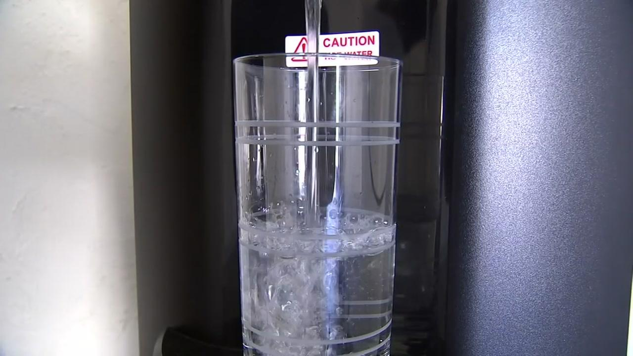 Water is poured into a glass from a water cooler at a home in Santa Rosa, Calif. on Thursday, Sept. 6, 2018.