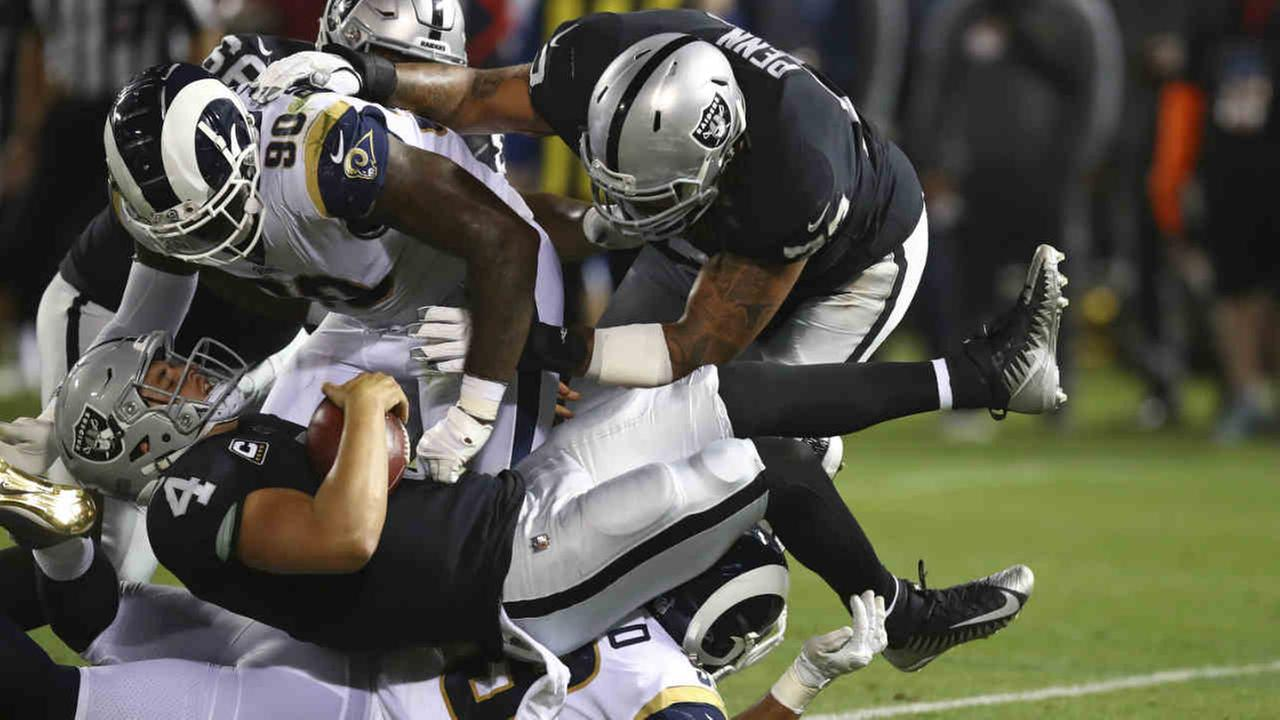 Oakland Raiders quarterback Derek Carr is brought down by Los Angeles Rams defensive tackle Michael Brockers (90) during an NFL game in Oakland, Calif., Monday, Sept. 10, 2018.