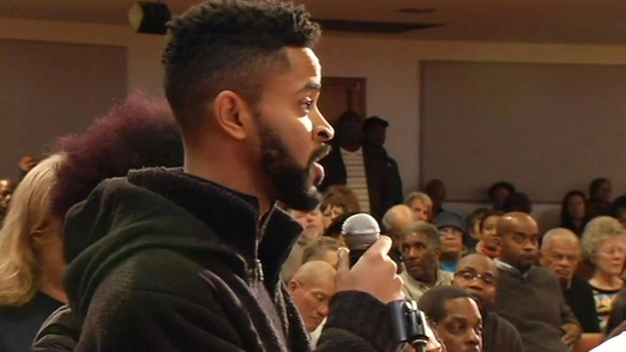 man speaks about police tactics at town hall meeting in Oakland