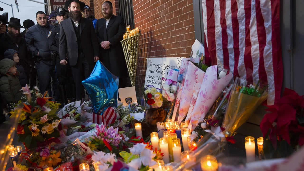 Prayers are said at a memorial, Sunday, Dec. 21, 2014, honoring two New York Police Department officers who were shot while sitting inside a patrol car. (AP Photo/Craig Ruttle)
