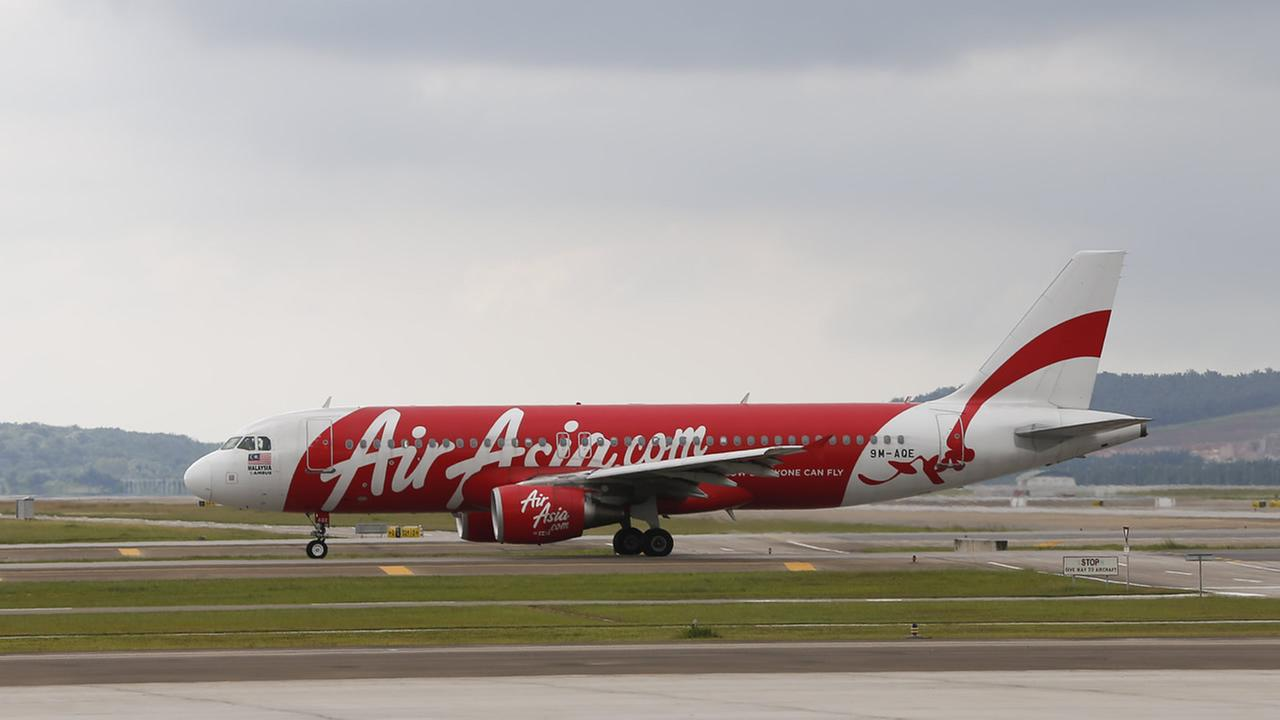 In this Nov. 26, 2014 photo, AirAsia Airbus A320-200 passenger jets are taxing on the tarmac at low cost terminal KLIA2 in Sepang, Malaysia.(AP Photo/Vincent Thian)