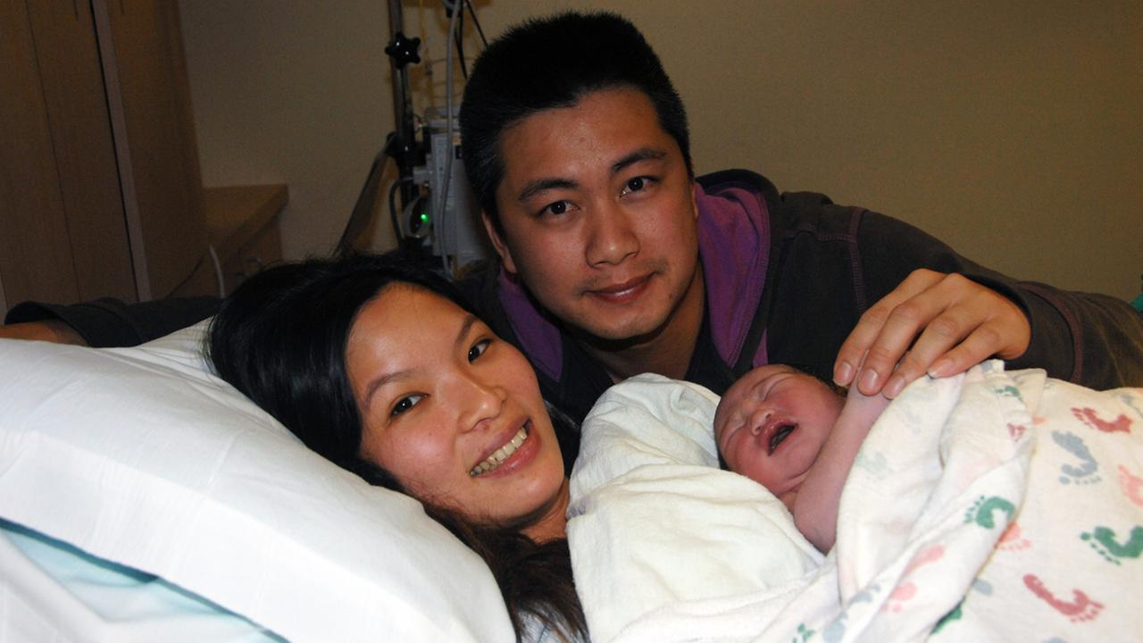 Proud mother YanFen Liang and father TakWa Tang hold the first baby born in the Bay Area in 2015.