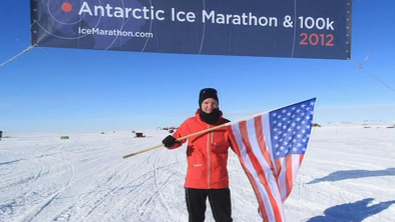 American Tim Durbin at the finish line of a marathon in Antarctica in 2012, holding a flag