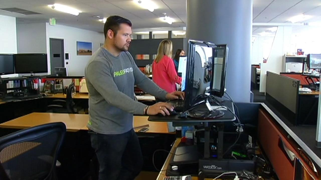 Workers using standing desks.