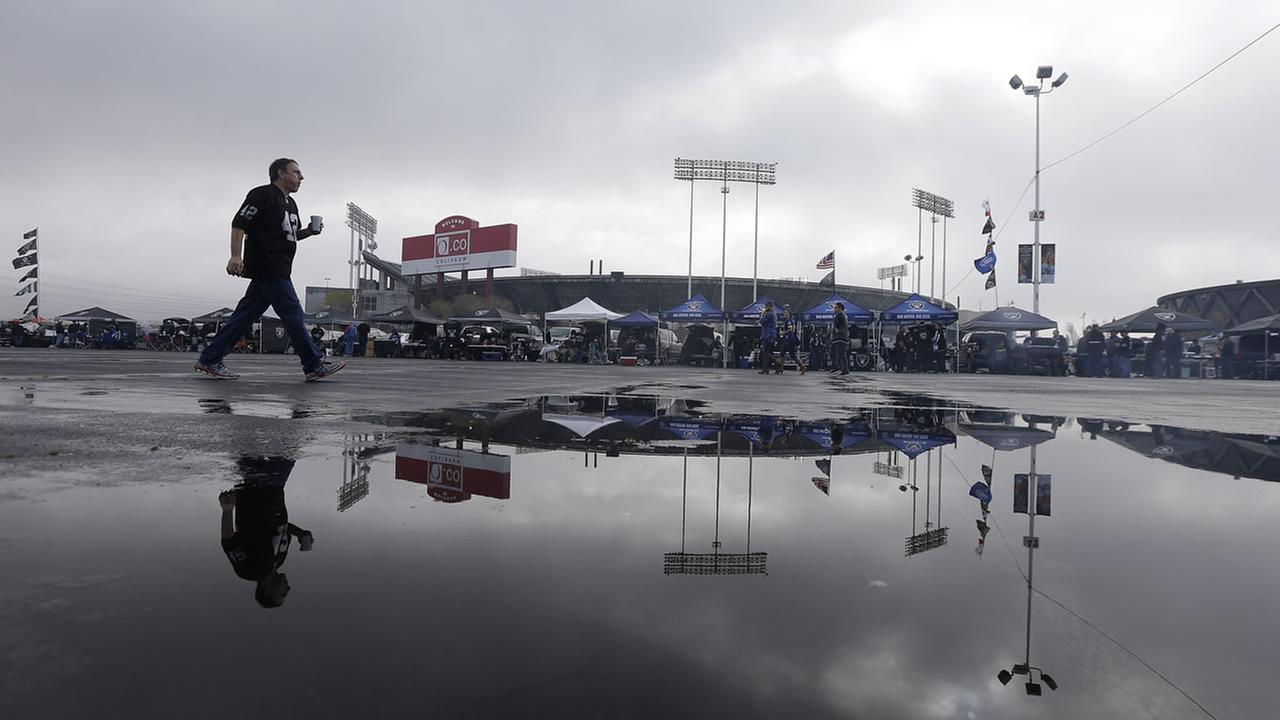 An Oakland Raiders fan walks past a puddle with a reflection of O.co Coliseum before an NFL football game in Oakland, Calif., Sunday, Dec. 21, 2014. (AP Photo/Jeff Chiu)