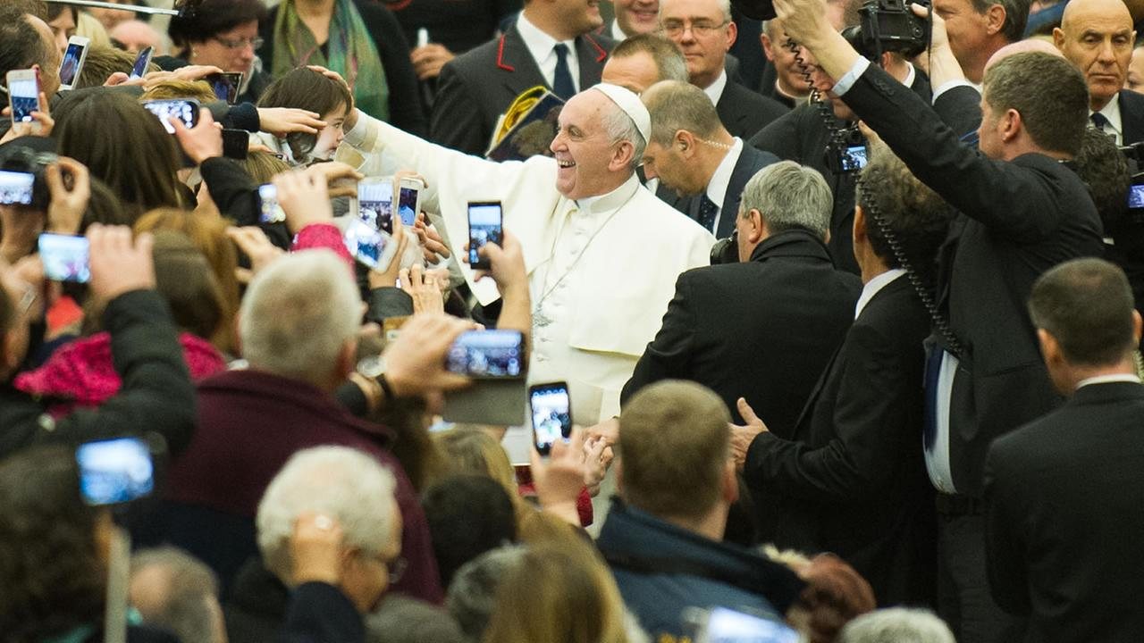 Pope Francis caresses a child as he arrives for his weekly general audience, in the Pope Paul II hall, at the Vatican, Wednesday, Jan. 28, 2015.