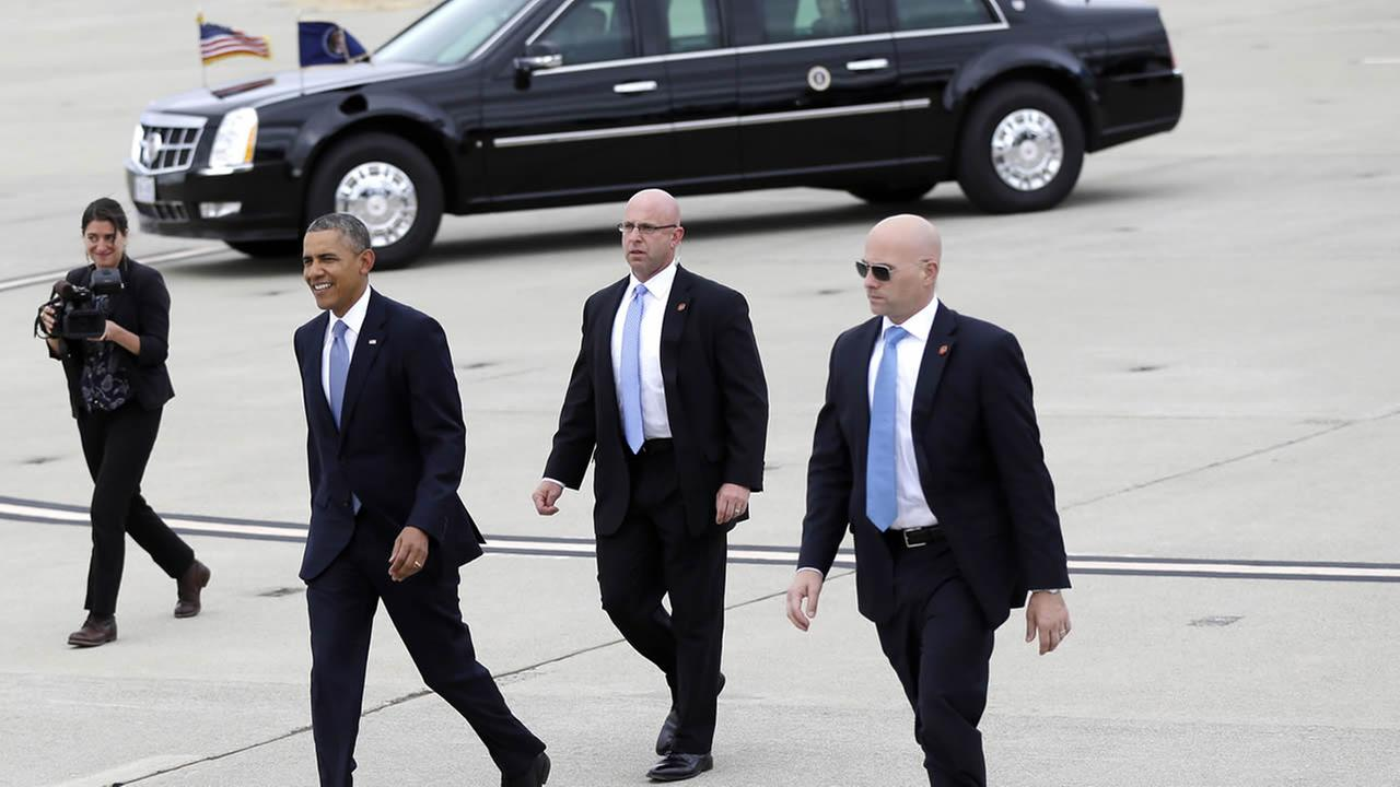 Pres. Obama is flanked by Secret Service agents as he arrives on Air Force One at Moffett Federal Airfield on May 8, 2014, in Mountain View, Calif. (AP Photo/Marcio Jose Sanchez)