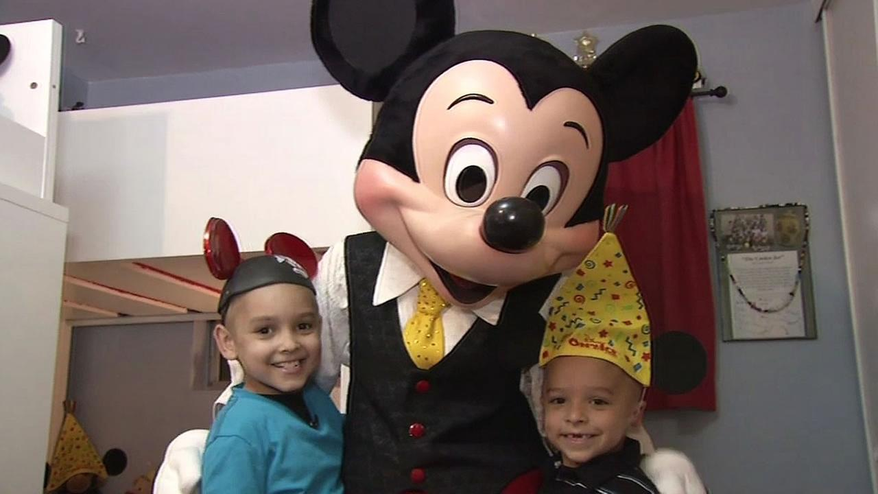 8-year-old Austin Bolender and his brother, 6-year-old Dominic hug Mickey Mouse