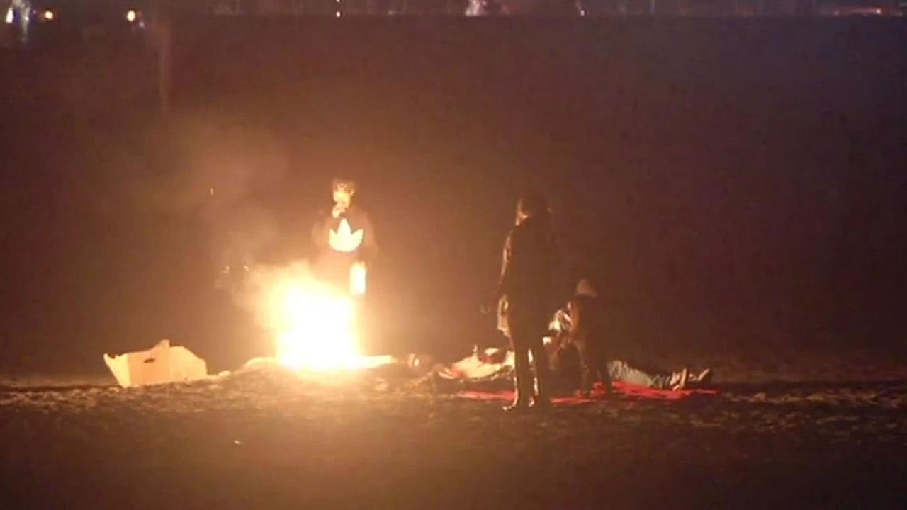 3 people stand around a bonfire at San Franciscos Ocean Beach