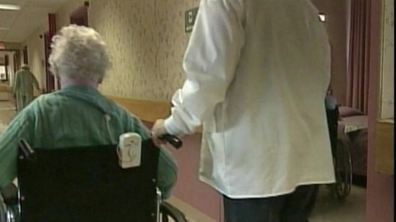 A medical professional walks an elderly woman in a wheelchair down a facilitys hallway.