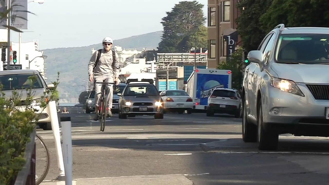 A man bikes down Polk Street in San Francisco.