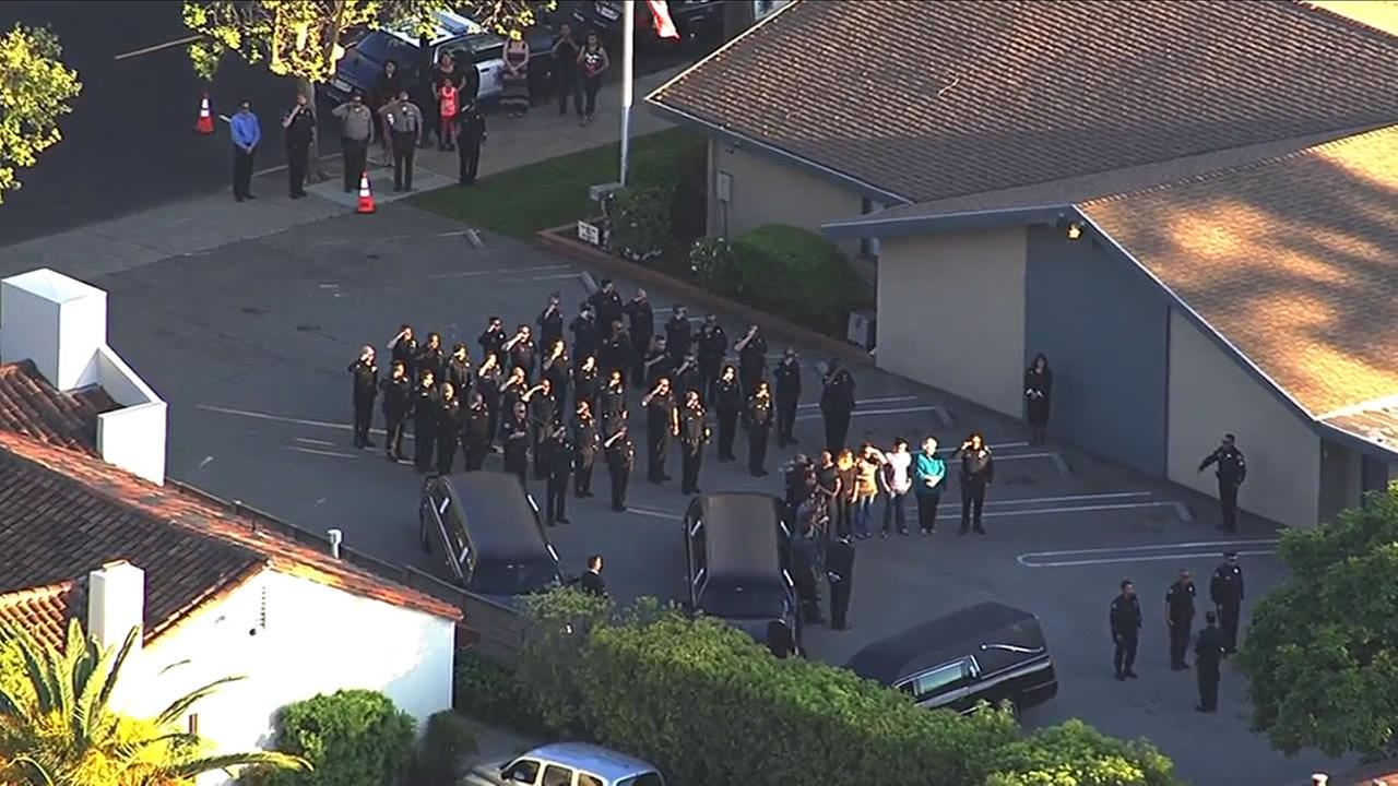Police salute Officer Michael Johnson as his body arrives at a funeral home in Los Gatos, Calif. on March 25, 2015.