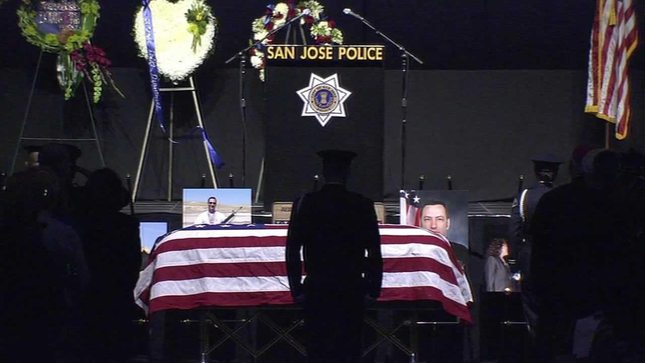 An officer stands in front of the casket of fallen SJPD Officer Michael Johnson
