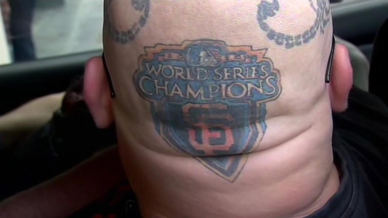 A fan shows off his tattoo with the San Francisco Giants logo at the teams home opener at AT&T Park on April 13, 2015.