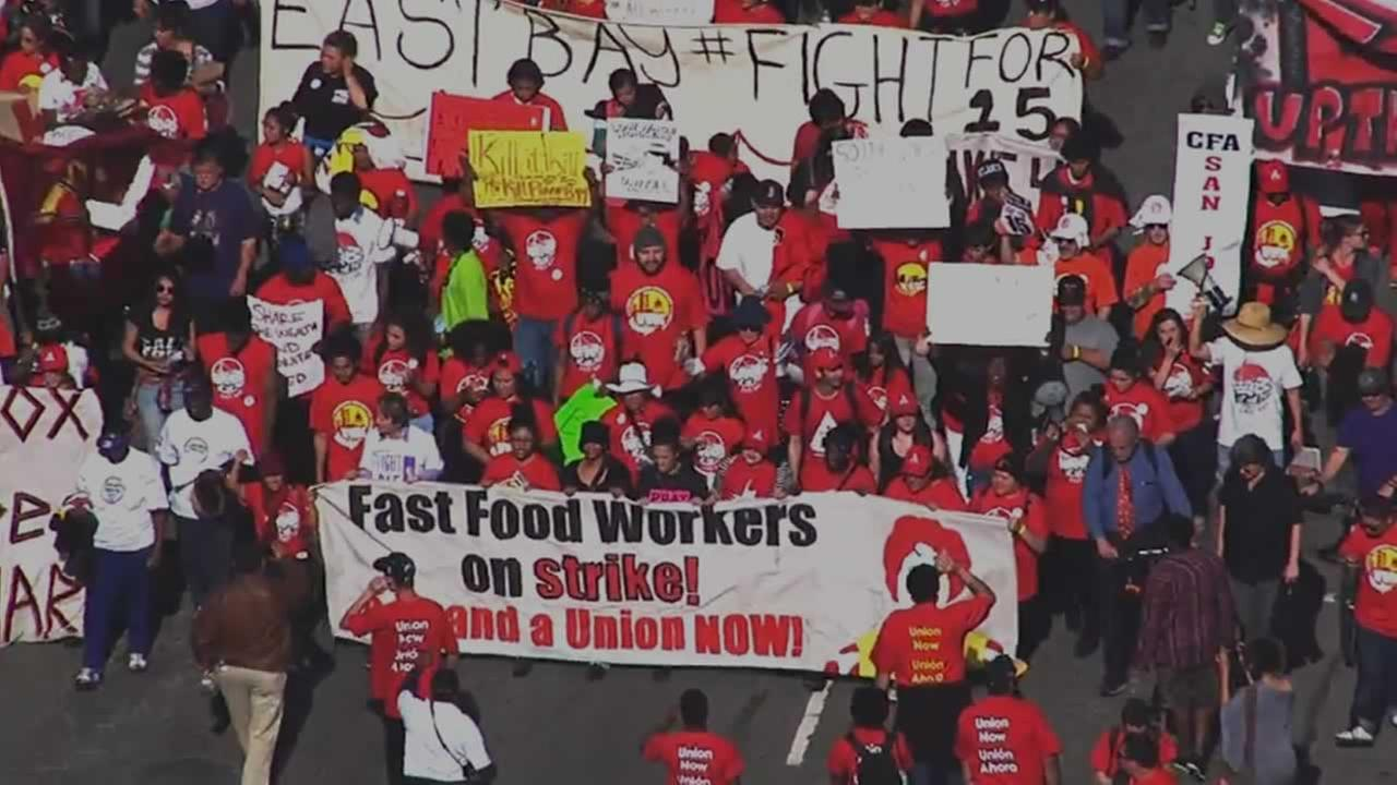 Demonstrators rallying for a wage hike for fast food workers march down Bancroft Avenue in Berkeley, Calif. On Wednesday, April 15, 2015.
