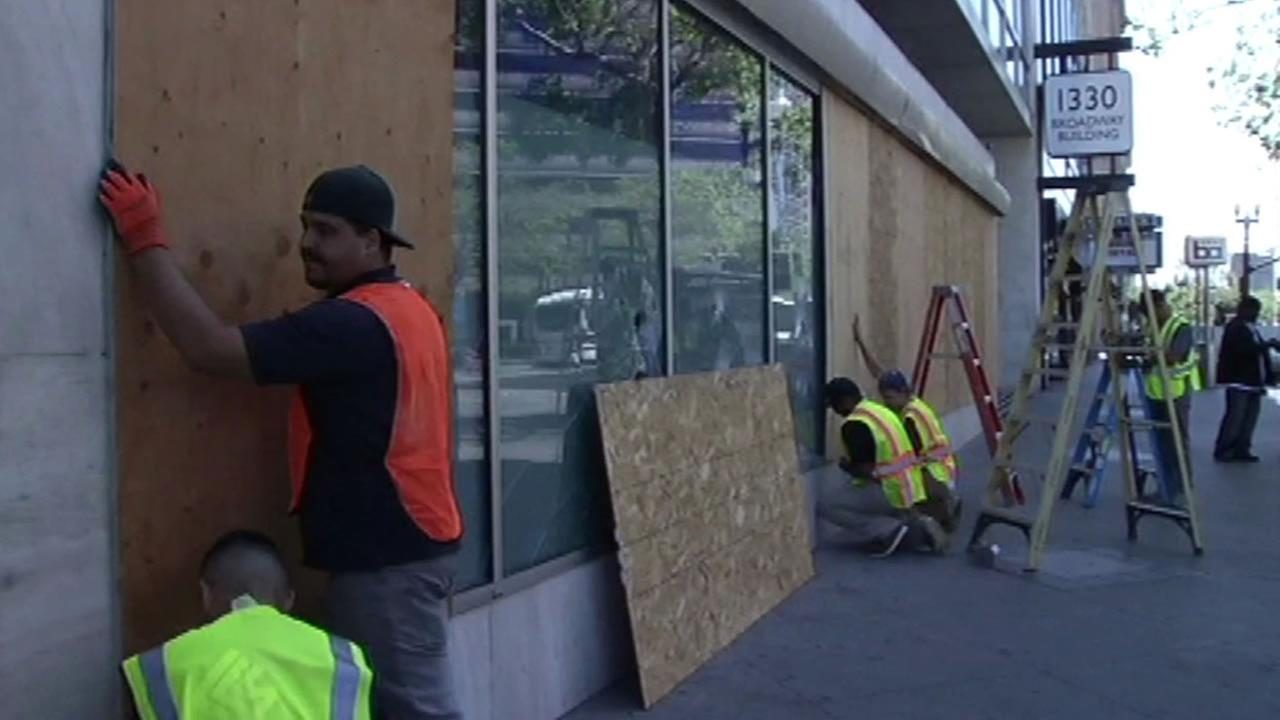 Businesses clean up after a destructive march through Oakland on May 1, 2015.