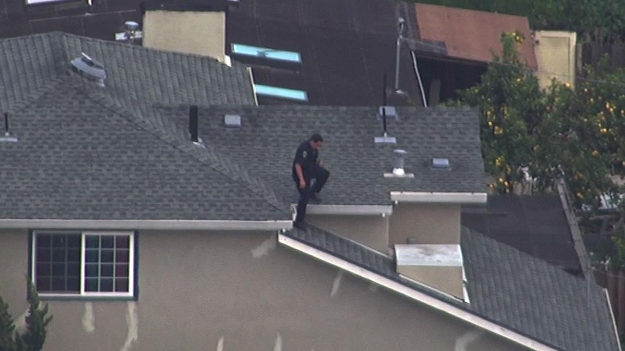 police officer walks on the roof of a home