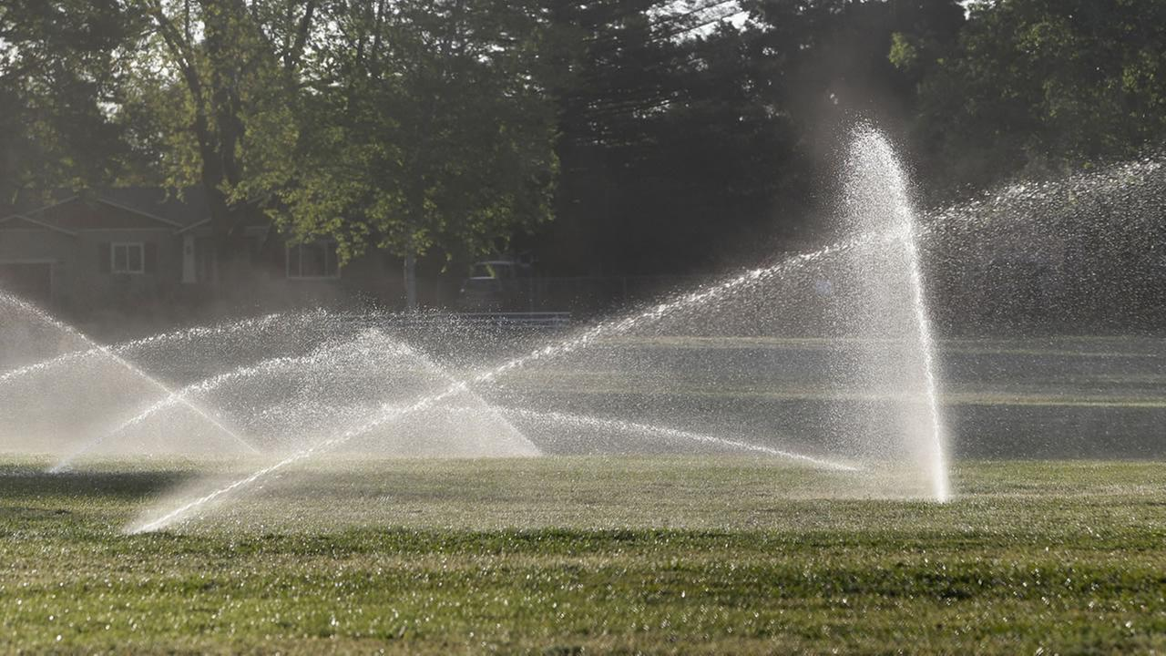 Sprinklers irrigate the field at Kit Carson Middle School in Sacramento, Calif., Wednesday, April 8, 2015.