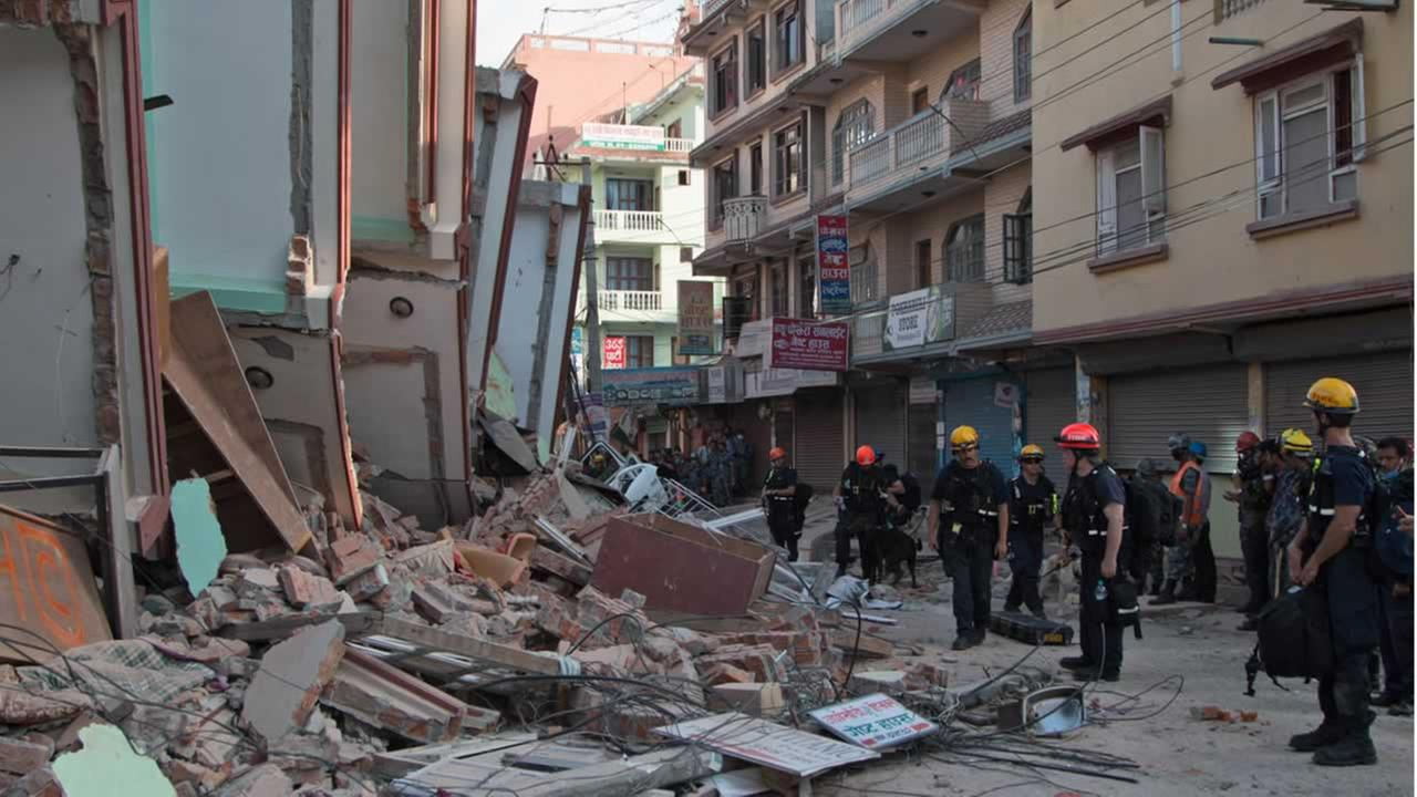 Rescue workers stand beside buildings that collapsed in an earthquake in Kathmandu, Nepal, Tuesday, May 12, 2015.
