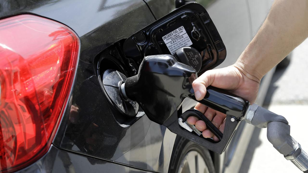 Gas station attendant Carlos Macar pumps gas in Andover, Mass., Friday, May 8, 2015. (AP Photo/Elise Amendola)