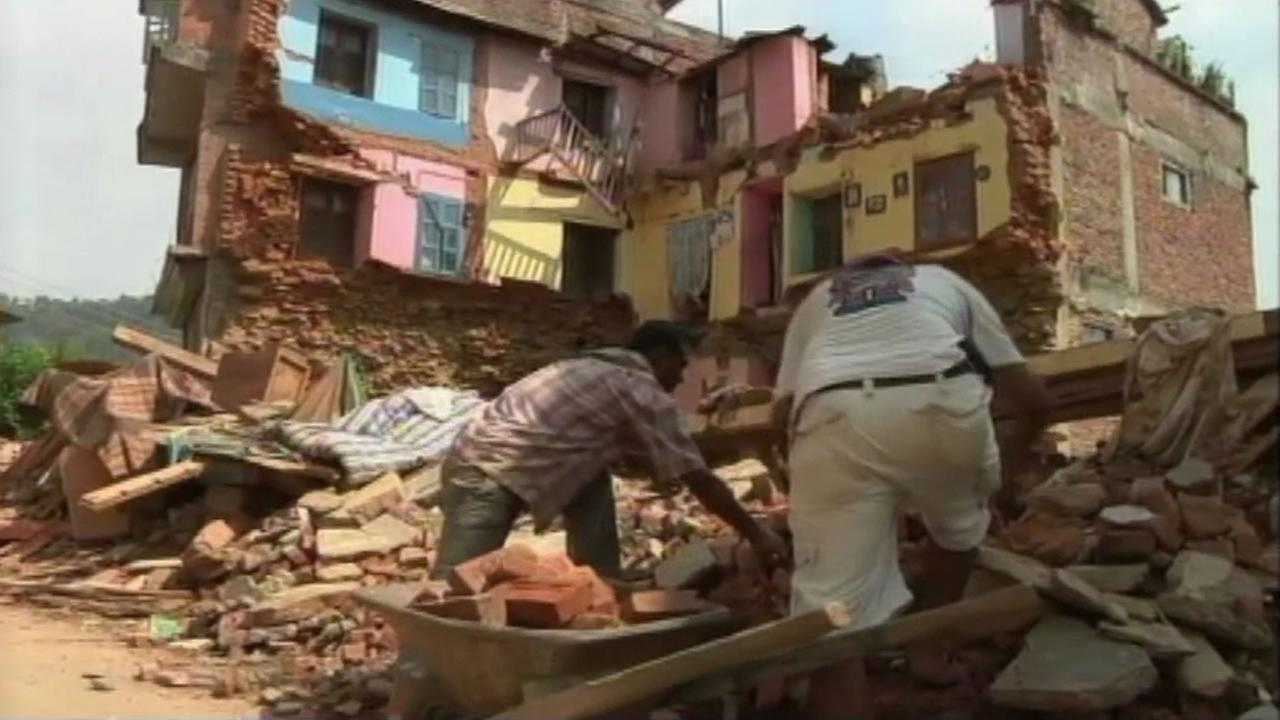 two men look at the rubble after two buildings collapses