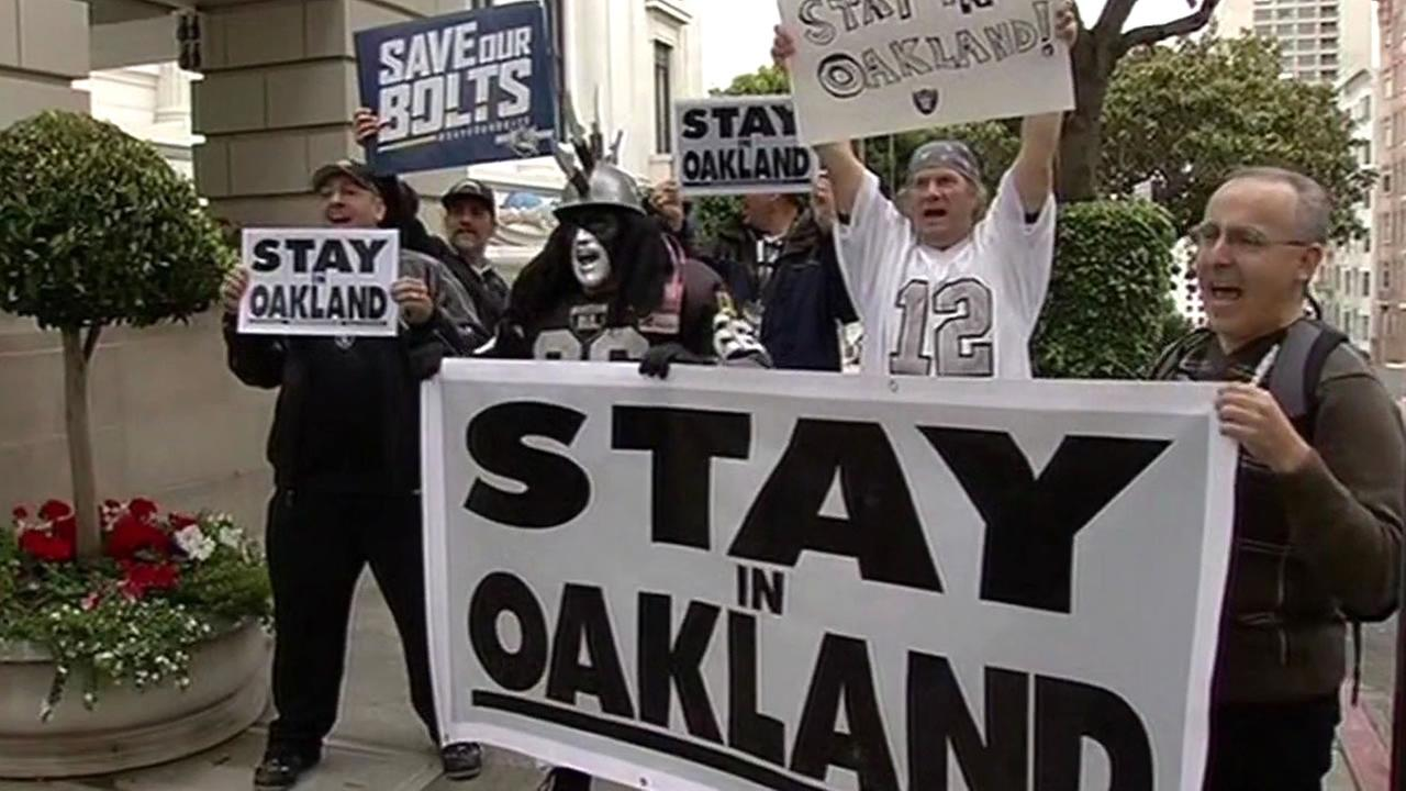Oakland Raiders fans hold signs saying Stay in Oakland
