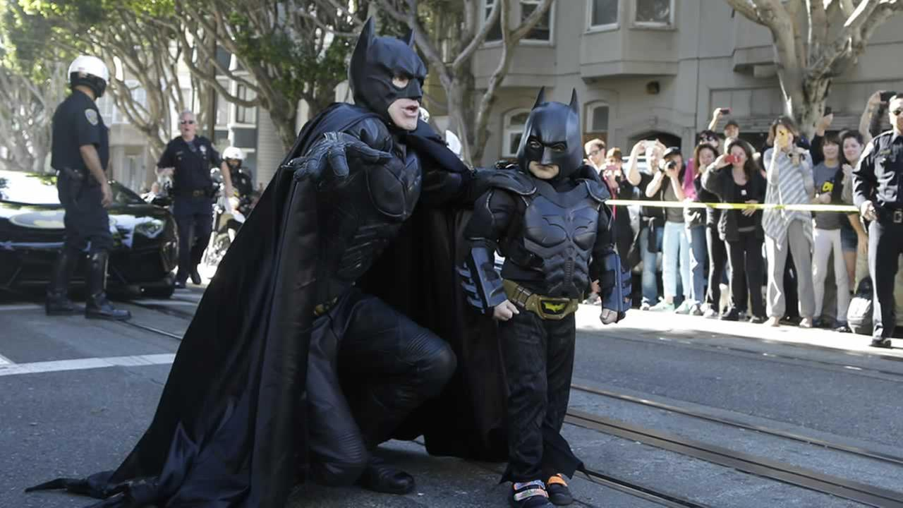 Miles Scott, dressed as Batkid, right, walks with Batman before saving a damsel in distress in San Francisco, Friday, Nov. 15, 2013.