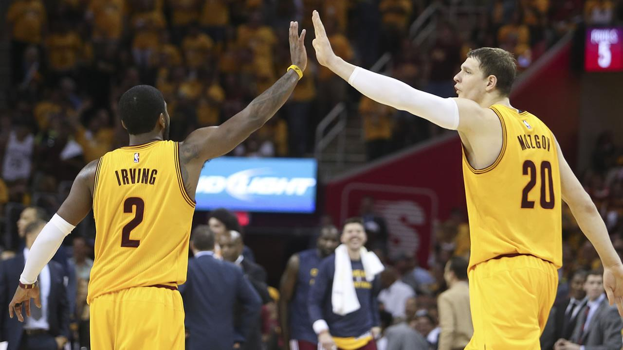 Cleveland Cavaliers Timofey Mozgov and Kyrie Irving high five each other