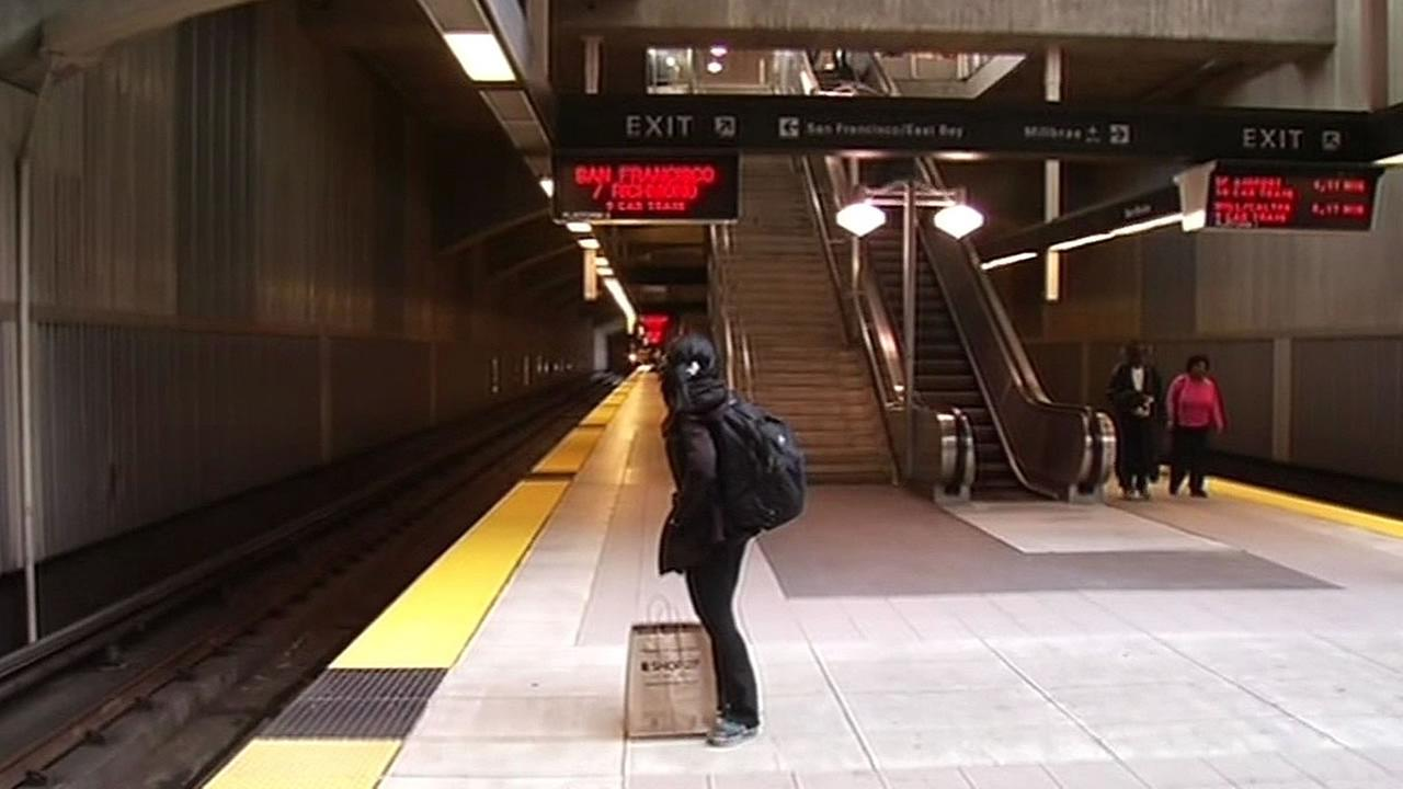 a woman stands waiting for a BART train