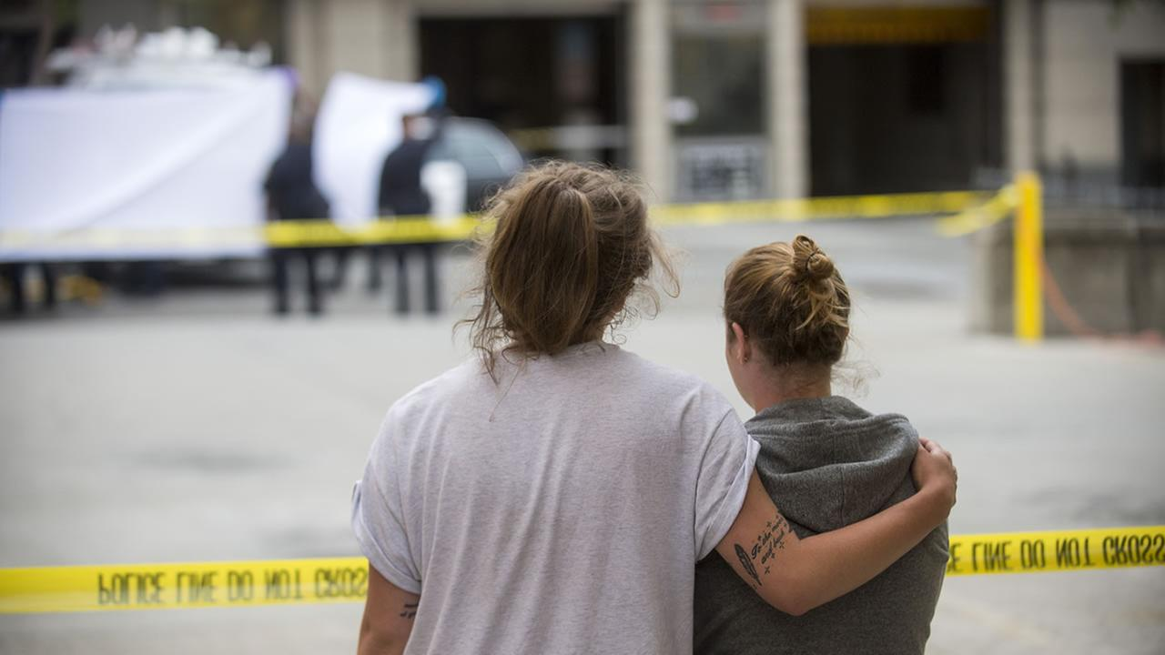 Two women embrace while watching sheriffs deputies move the body of a person who died when a fourth floor balcony collapsed in Berkeley, Calif. on Tuesday, June 16, 2015. (AP Photo/Noah Berger)
