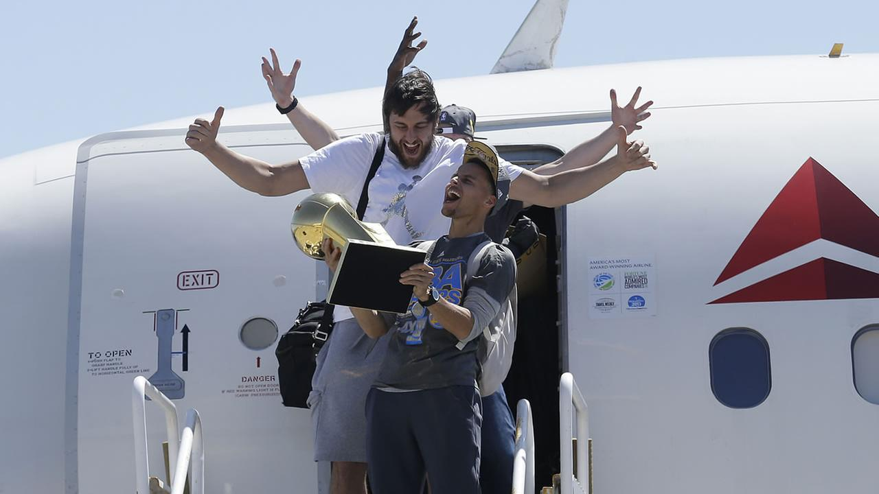 Warriors guard Stephen Curry, carries the Larry OBrien championship trophy in front of center Andrew Bogut after the team landed in Oakland, Calif., June 17, 2015.  (AP Photo/Jeff Chiu)
