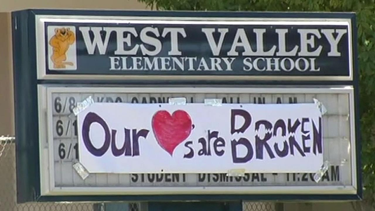 handmade sign that reads Our hearts are breaking