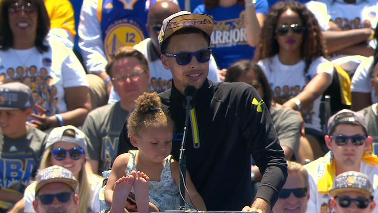 Warriors Stephen Curry and his daughter, Riley, stand at the podium during the teams victory parade on Friday, June 19, 2015.